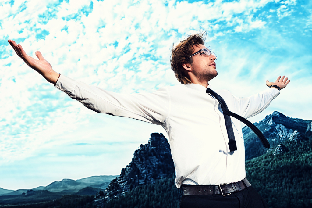 Successful business man standing on a peak of the mountain and p
